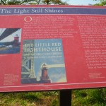 "A placard tells the publishing story of ""The Little Red Lighthouse and the Great Gray Bridge."""